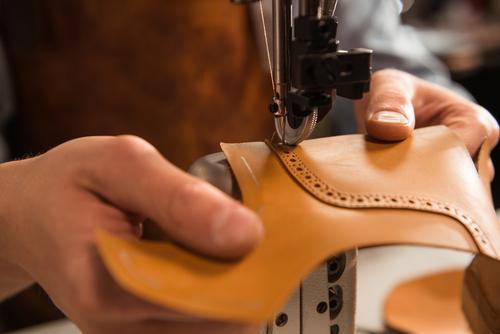 Gros plan d'un cordonnier piquant une partie de la chaussure dans un atelier.